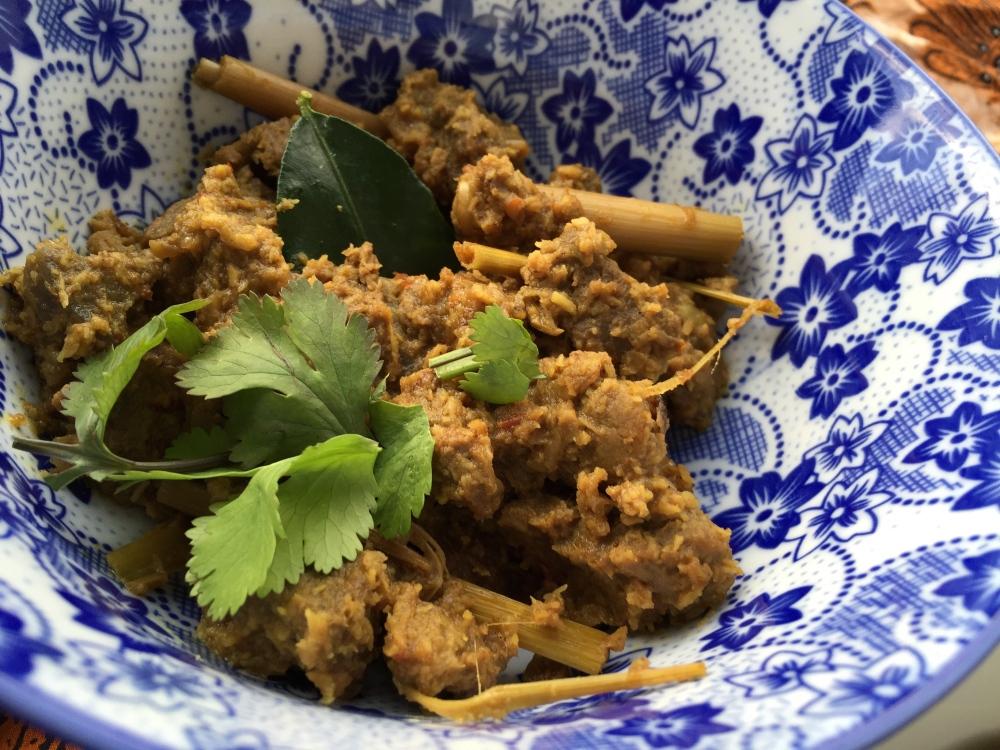 op dit plaatje zie je Rendang met verse koriander (ketumbar), een enkel blaadje limoen (daun jeruk purut) en serehstengel.